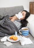 Ung kvinna som har influensa som blåser hennes näsa Arkivfoto