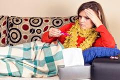 Ung kvinna som har influensa och tar hennes temperatur Royaltyfri Bild
