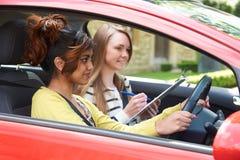 Ung kvinna som har körningskurs med den kvinnliga instruktören Arkivfoton