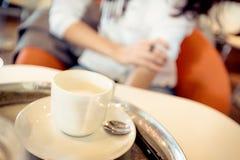 Ung kvinna som har kaffe i ett kafé Arkivbild