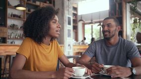 Ung kvinna som har kaffe med hennes vän i kafé lager videofilmer