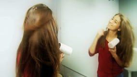 Ung kvinna som har långt silkeslent hår för rolig uttorkning arkivfilmer
