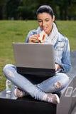 Ung kvinna som har lunch i park genom att använda bärbar dator Fotografering för Bildbyråer