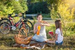 Ung kvinna som har picknicken vid floden med 10 år gammal daughte Arkivfoton