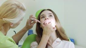 Ung kvinna som har tandundersökning på tandläkareProfessional den muntliga undersökningen arkivfilmer