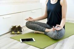 Ung kvinna som hemma övar att göra yoga arkivbilder