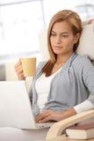 Ung kvinna som hemma använder bärbar dator Arkivfoto