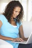 Ung kvinna som hemma använder bärbar datordatoren Arkivbild