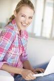 Ung kvinna som hemma använder bärbar datordatoren Royaltyfria Bilder
