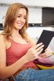 Ung kvinna som hemma använder den Digital minnestavlan Arkivbild