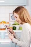 Ung kvinna som hemma använder en minnestavladator Fotografering för Bildbyråer