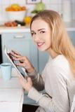 Ung kvinna som hemma använder en minnestavladator Arkivfoton