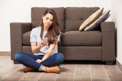 Ung kvinna som hemma använder en smartphone Royaltyfria Bilder