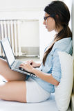 Ung kvinna som hemma använder hennes bärbar dator Royaltyfri Foto