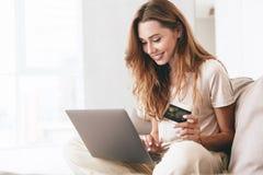 Ung kvinna som hemma arbetar med bärbara datorn och kreditkorten arkivbilder