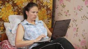 Ung kvinna som hemma arbetar på bärbara datorn på soffan Uppmärksamt pressar på touchpaden stock video
