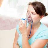 Ung kvinna som hemma gör inandning med en nebulizer arkivbild