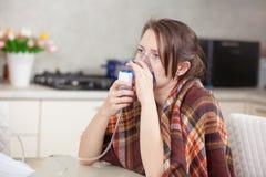 Ung kvinna som hemma g?r inandning med en nebulizer royaltyfri foto