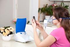 Ung kvinna som hemma g?r inandning med en nebulizer royaltyfria bilder