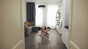 Ung kvinna som hemma g?r konditiongenomk?raren f?r sund livsstil l?ngsam r?relse Sund och sportlivsstil arkivfilmer