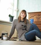 Ung kvinna som hemma kopplar av Royaltyfria Foton