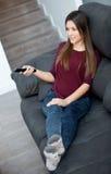 Ung kvinna som hemma kopplar av hållande ögonen på TV Royaltyfria Bilder