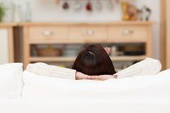 Ung kvinna som hemma kopplar av på en soffa arkivbild