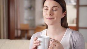 Ung kvinna som hemma kopplar av på soffan Nätt kvinnligt dricka kaffe eller te från koppen i vardagsrum arkivfilmer