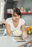 Ung kvinna som hemma lagar mat genom att använda den digitala minnestavlan för recept Royaltyfria Bilder