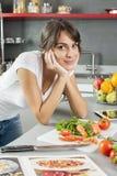 Ung kvinna som hemma lagar mat genom att använda den digitala minnestavlan för recept Arkivfoto