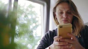 Ung kvinna som hemma sitter och använder hennes smartphone arkivfilmer