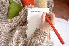 Ung kvinna som hemma skrivar ett brev till jultomten Royaltyfria Bilder