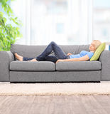 Ung kvinna som hemma sover på en modern soffa royaltyfria bilder