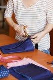 Ung kvinna som hemma syr och att fålla blått tyg Modeformgivare som skapar nya innegrejstilar Sömmerskan gör Royaltyfri Fotografi