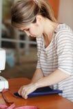 Ung kvinna som hemma syr och att fålla blått tyg Modeformgivare som skapar nya innegrejstilar Sömmerskan gör kläder via annons Arkivbilder