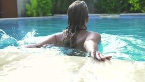 Ung kvinna som hoppar i simbassäng på sommarsemesterort Attraktiv flickasimning i utomhus- pöl för blått vatten i semesterort lager videofilmer