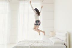 Ung kvinna som hoppar upp med händer som lyfts upp fotografering för bildbyråer