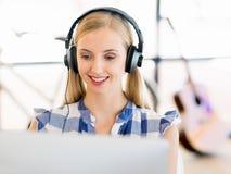 Ung kvinna som i regeringsställning arbetar med hörlurar Royaltyfri Fotografi