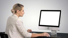 Ung kvinna som i regeringsställning arbetar och att sitta på skrivbordet som ser bildskärmen på lutningbakgrund arkivbild