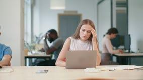 Ung kvinna som i regeringsställning får det dåliga brevet på bärbara datorn Ledsen frilans- kvinna lager videofilmer