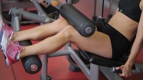 Ung kvinna som inomhus gör placerad benkrullning i sportklubba Den attraktiva idrottsman nen förbereder ben och bakdelar stock video