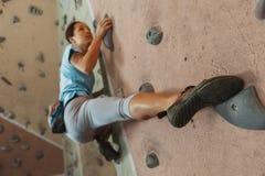 Ung kvinna som inomhus klättrar Arkivfoto