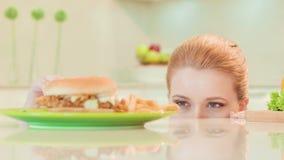 Ung kvinna som inte väljer mellan sund mat och arkivfilmer