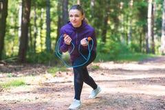 Ung kvinna som joggar och gör övningar i den soliga skogen royaltyfria foton