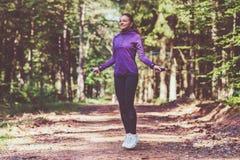 Ung kvinna som joggar och gör övningar i den soliga skogen arkivfoton