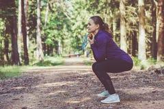 Ung kvinna som joggar och gör övningar i den soliga skogen arkivbilder