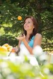 Ung kvinna som jonglerar apelsiner på henne som är trädgårds- Arkivbild