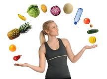 Ung kvinna som jonglerar frukter och grönsaker Fotografering för Bildbyråer
