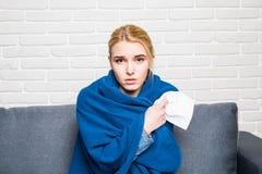 Ung kvinna som känner sig sjuk, eller ledset som slås in i hemtrevlig blå filt och hemma sitter på soffan Royaltyfri Foto