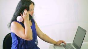 Ung kvinna som kör en bärbar dator och en start för att tala på hennes telefon
